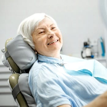 Smiling dental patient looking at her reflection in a mirror