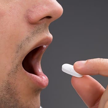 Man taking oral conscious sedative pill