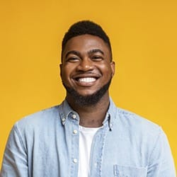 man smiling against a yellow background