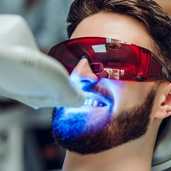 person getting their teeth whitened in a dentist's office