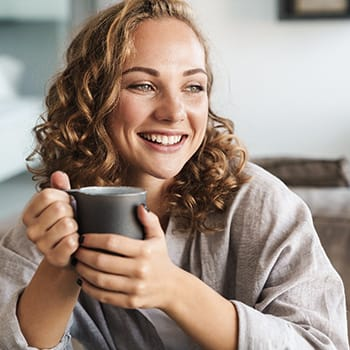person smiling and drinking tea after getting their teeth whitened