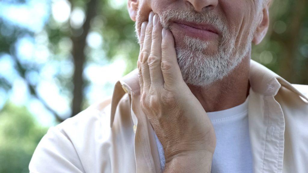 Closeup of man experiencing jaw soreness